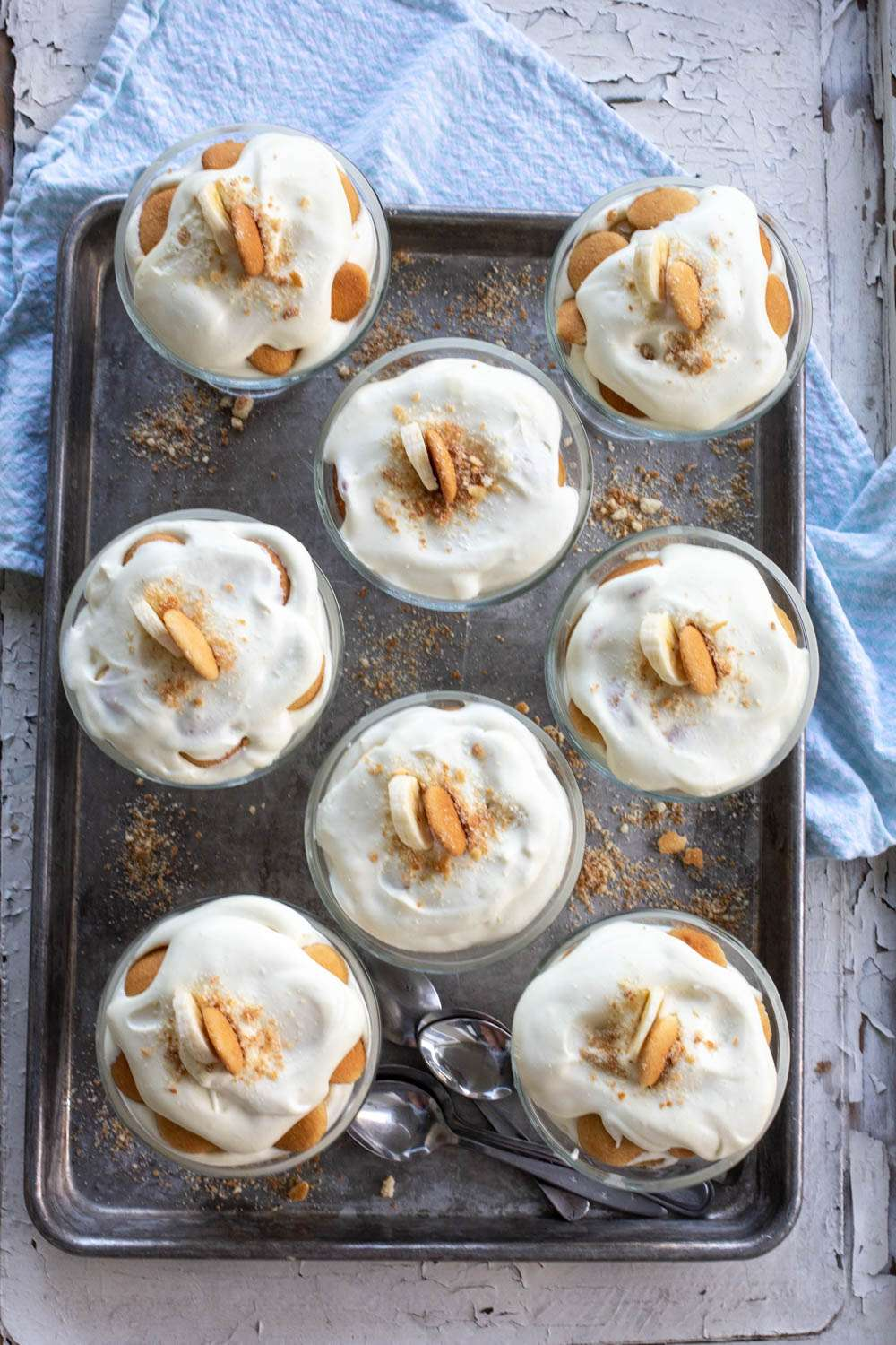 Magnolia Bakery Banana Pudding in glass bowls with spoons on cookie sheet. Looking down from top.