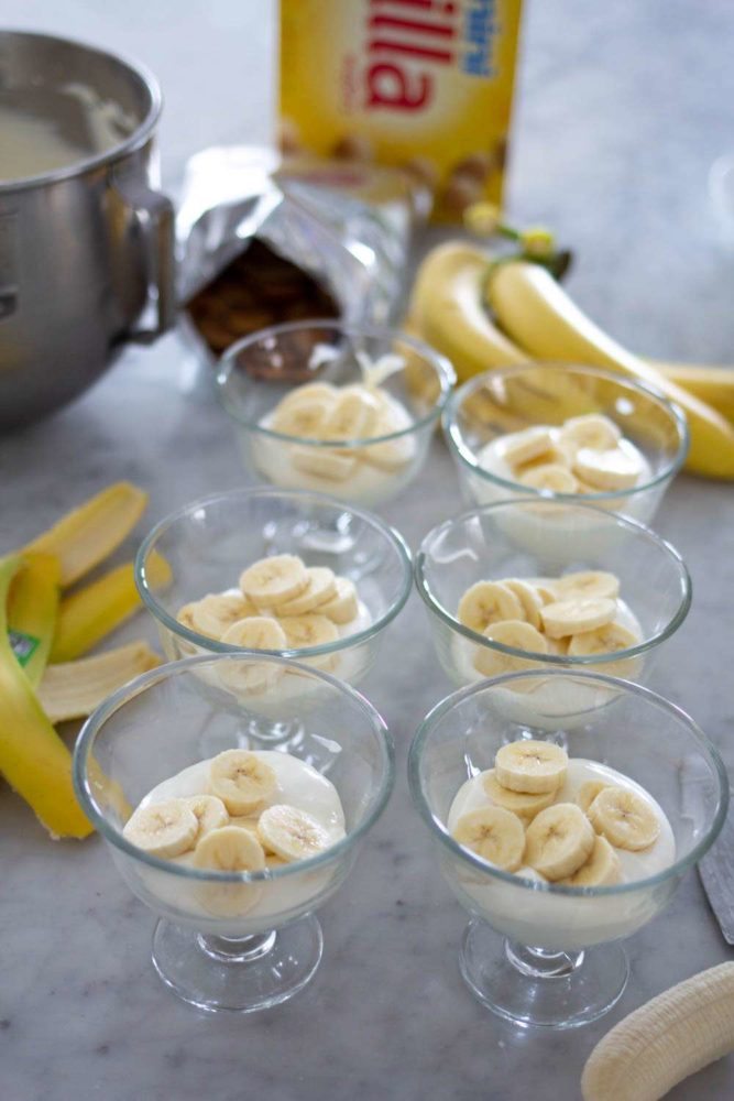 Small glass bowls with sliced bananas, bananas in background and Nilla Wafers box