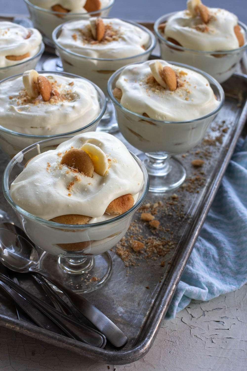 Magnolia Bakery Banana Pudding in small glass bowls with spoons on a cookie sheet.