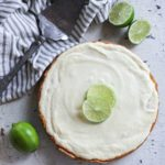 Key Lime Pie with limes and serving utensil