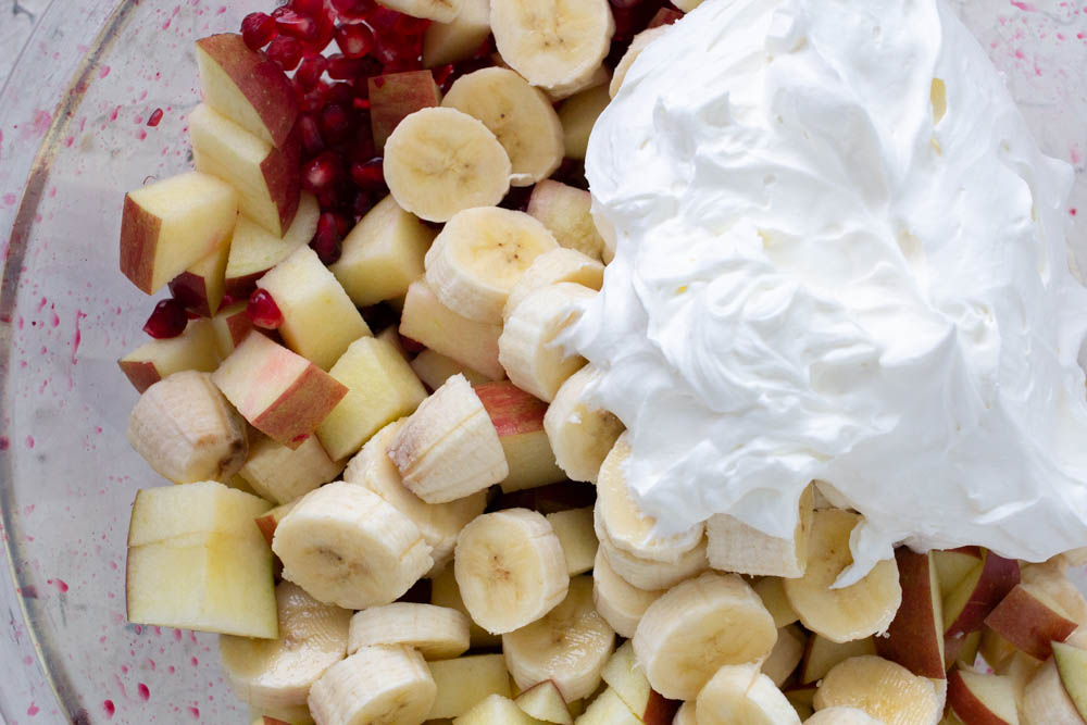 Apple, banana, pomegranate salad with whipped cream